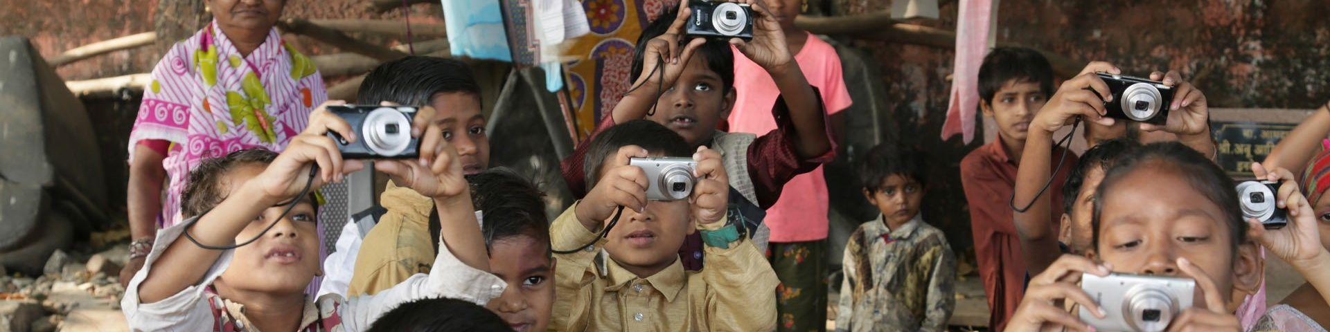 Little children in a group, holding their Canon cameras up to take a photo.